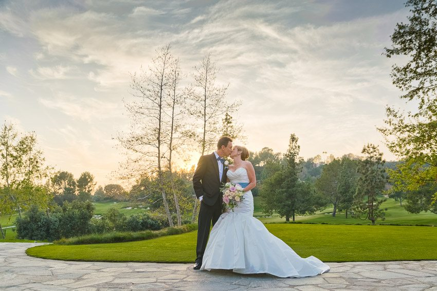 bride and groom kissing on the golf course