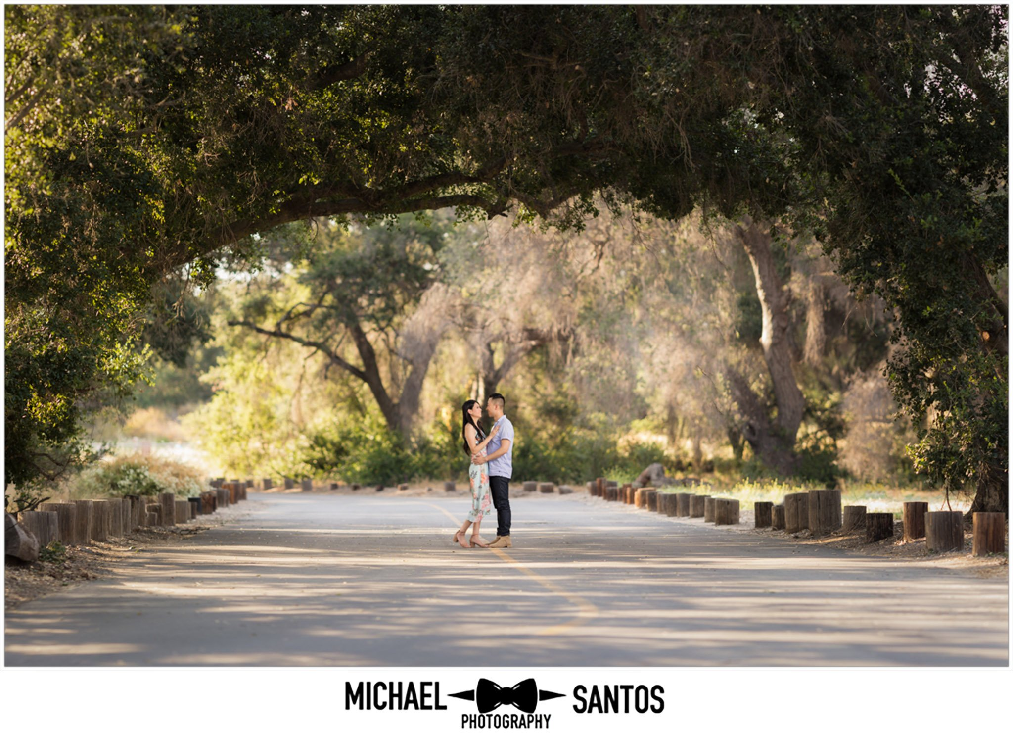 couple standing under a tree archway in capsers wilderness park for their portrait session