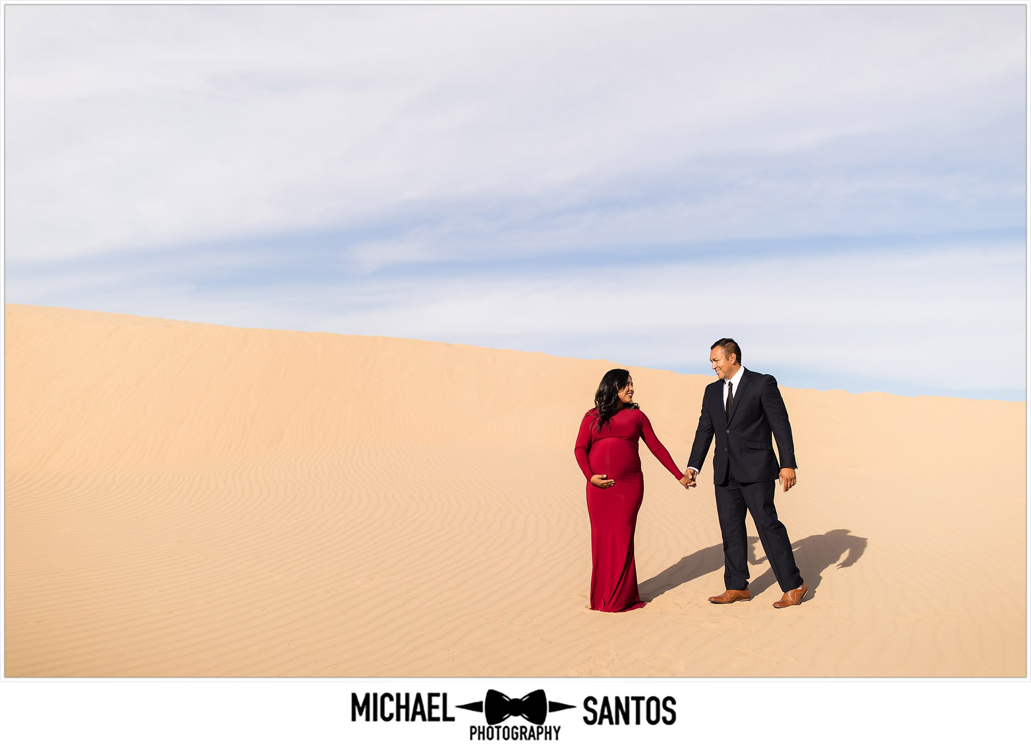 expecting parents walking in the sand dunes during their maternity photography session